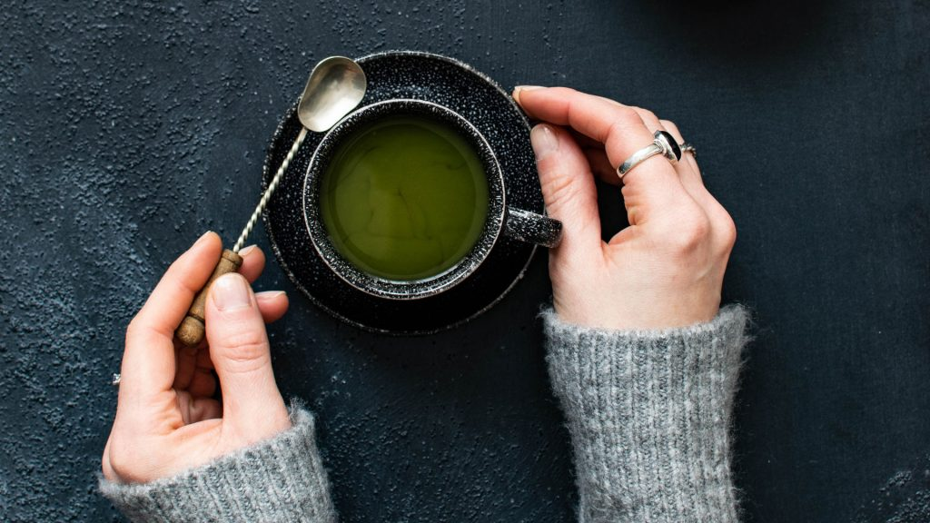 woman-holding-cup-of-green-tea